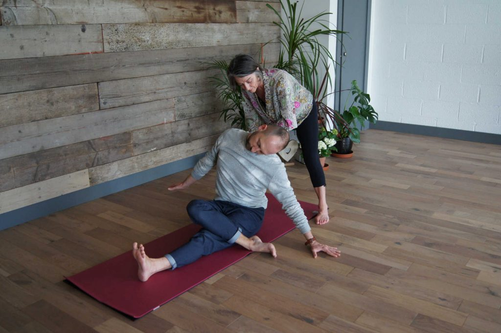 woman showing man a yoga position on a mat