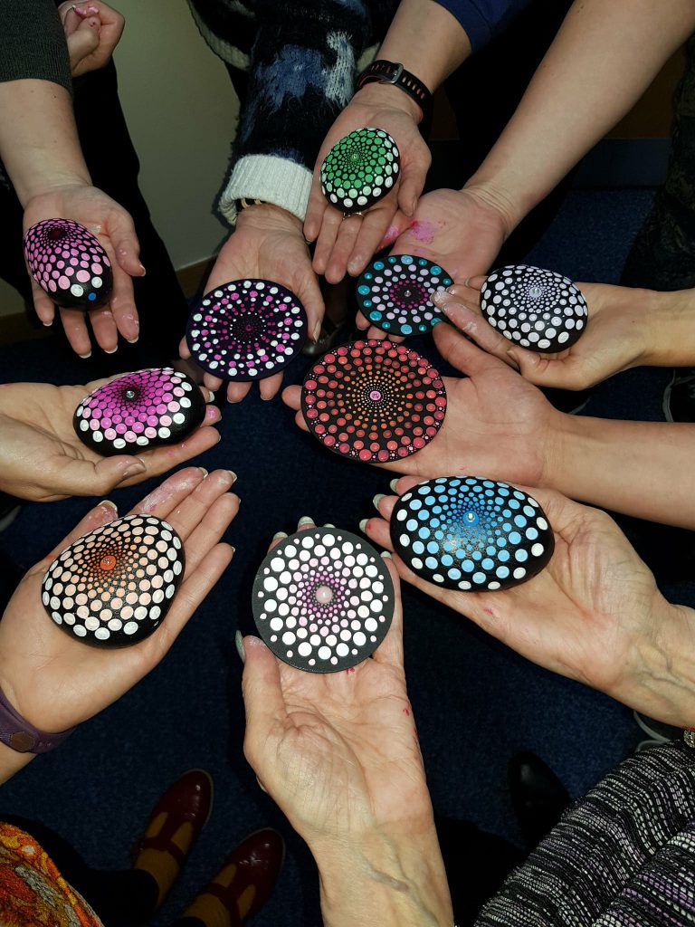 people holding mandalas in a circle