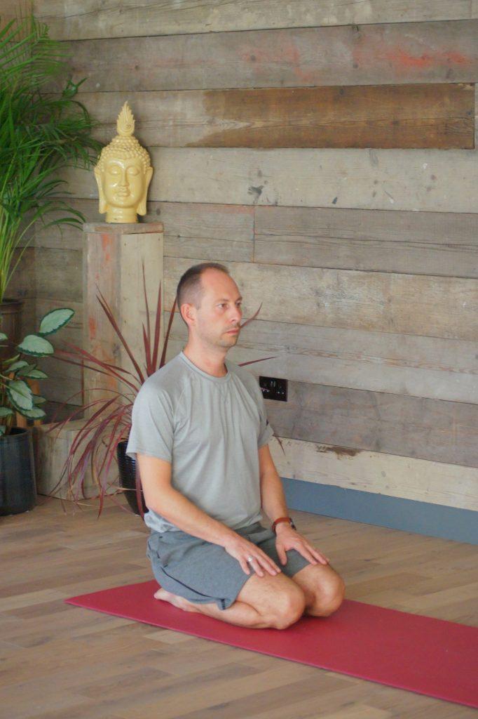 yoga practitioner kneeling on mat in yoga studio